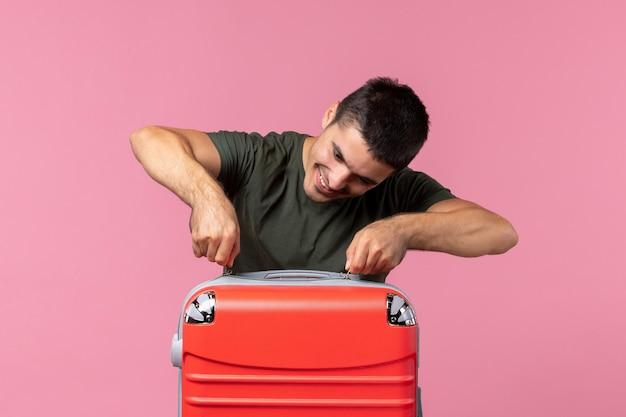 Vista frontal joven varón preparándose para las vacaciones y sintiéndose feliz en el espacio rosa claro