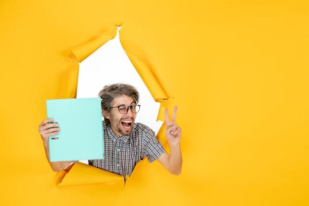Vista frontal joven varón sosteniendo archivo verde sobre fondo amarillo color trabajo año nuevo navidad oficina emoción trabajo vacaciones