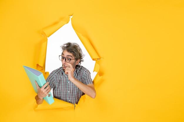 Vista frontal joven varón sosteniendo el archivo verde sobre fondo amarillo trabajo color trabajo oficina emoción vacaciones navidad