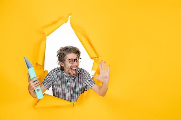 Vista frontal joven varón sosteniendo el archivo verde sobre fondo amarillo trabajo oficina de trabajo emoción vacaciones trabajo de navidad