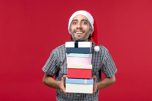 Vista frontal joven varón sosteniendo regalos de año nuevo sobre fondo rojo.