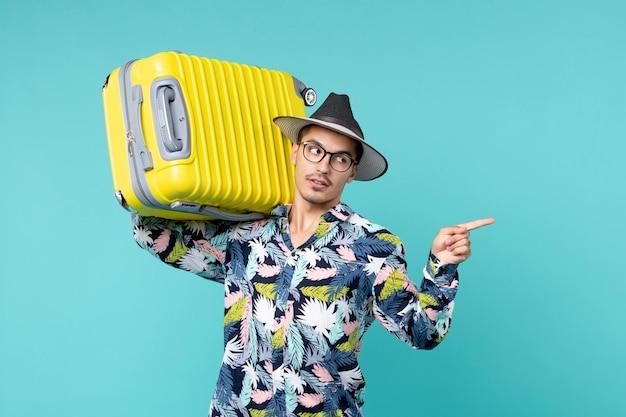 Vista frontal del joven varón de vacaciones y sosteniendo su bolsa amarilla en el espacio azul