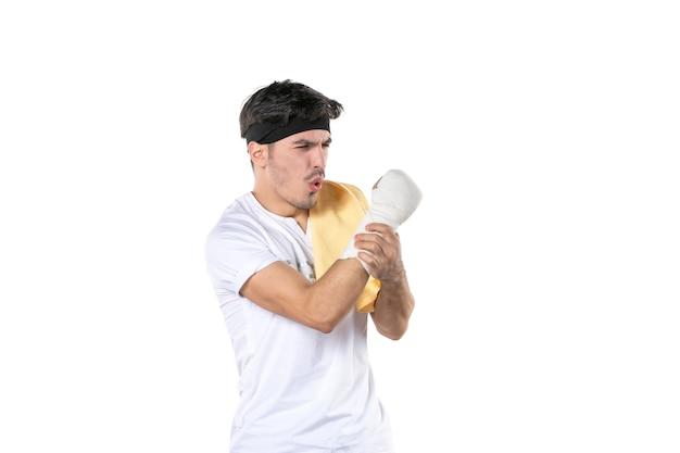 Vista frontal joven con vendaje en su mano herida sobre fondo blanco ajuste gimnasio atleta dolor estilo de vida deporte dieta lesión