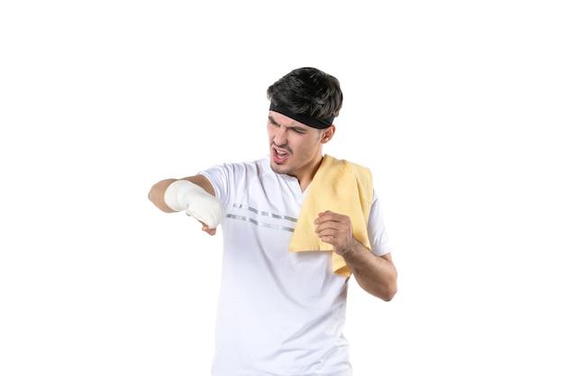 Vista frontal joven con vendaje en su mano herida sobre fondo blanco ajuste gimnasio atleta dolor estilo de vida deporte lesión corporal