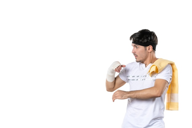 Vista frontal joven con vendaje en su mano herida sobre fondo blanco en forma atleta gimnasio dieta deporte dolor lesión cuerpo estilo de vida hospital
