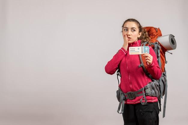 Vista frontal del joven viajero confundido con mochila grande sosteniendo un boleto de viaje con espacio libre