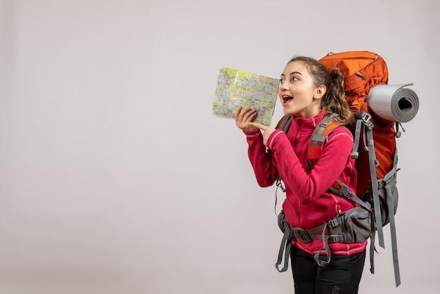 Vista frontal del joven viajero feliz con mochila grande sosteniendo el mapa