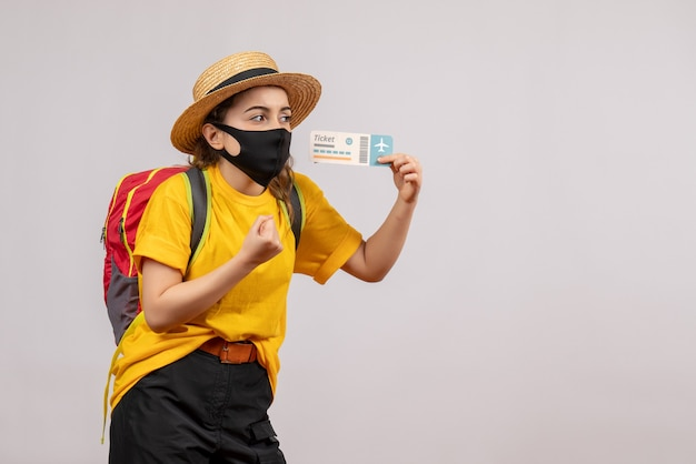 Vista frontal del joven viajero lindo con mochila sosteniendo el boleto de viaje en la pared gris aislada