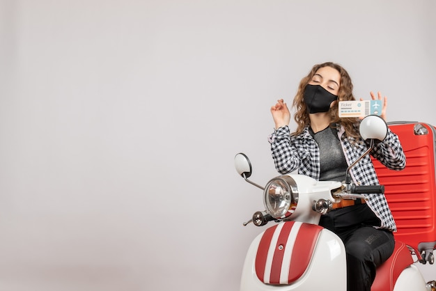 Vista frontal joven viajero con máscara negra en ciclomotor sosteniendo billete de viaje cerrando los ojos