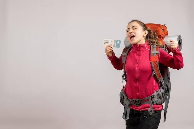 Vista frontal del joven viajero con mochila grande sosteniendo el boleto de viaje