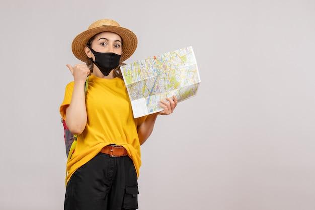 Vista frontal joven viajero con mochila sosteniendo mapa apuntando hacia atrás