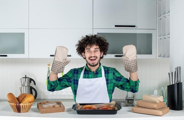 Vista frontal del joven vistiendo titular de pie detrás de la mesa pasteles recién horneados en la cocina