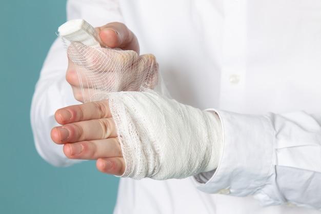 Una vista frontal joven vistiendo vendaje estéril en traje médico blanco
