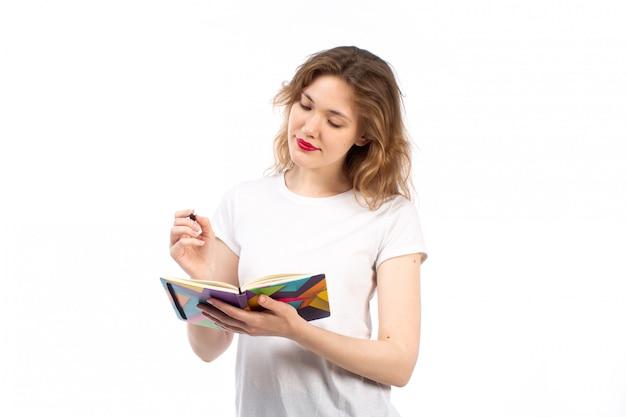 Una vista frontal jovencita en camiseta blanca escribiendo notas sobre el blanco