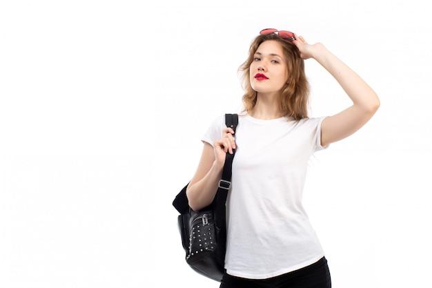 Una vista frontal jovencita en camiseta blanca gafas de sol rojas bolso negro sobre el blanco