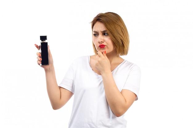 Una vista frontal jovencita en camiseta blanca con tubo de perfume negro expresión no segura en el blanco