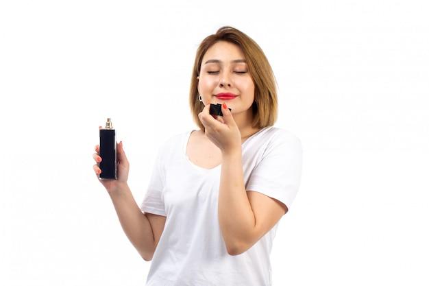 Una vista frontal jovencita en camiseta blanca con tubo de perfume negro que huele en el blanco