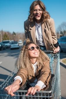 Vista frontal jovencita posando con carrito de compras