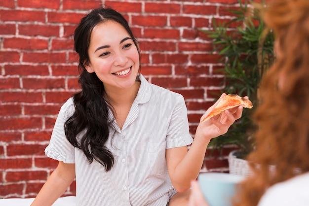 Vista frontal jóvenes amigos compartiendo pizza
