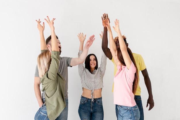Vista frontal jóvenes amigos con manos levantadas