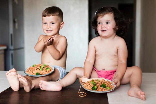Vista frontal jóvenes hermanos en la cocina