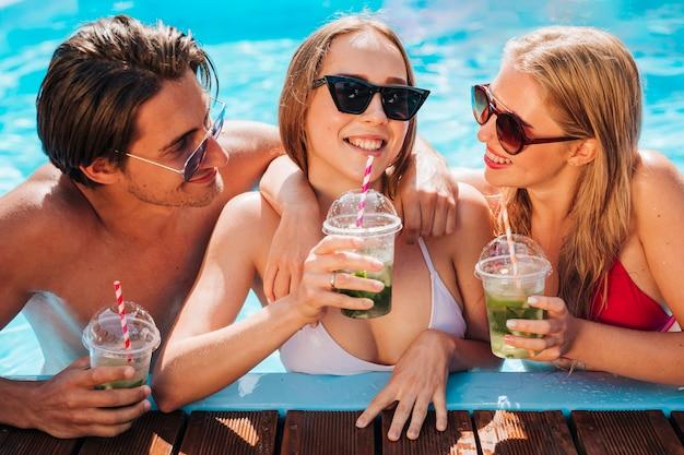 Vista frontal de los jóvenes relajándose en la piscina.