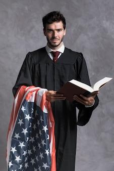 Vista frontal juez con bandera y libro abierto