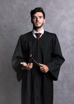 Vista frontal juez en bata con mazo de madera