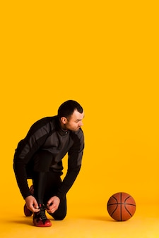 Vista frontal del jugador de baloncesto masculino atar cordones de los zapatos con balón y espacio de copia