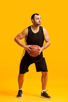 Vista frontal del jugador de baloncesto masculino posando con balón