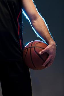 Vista frontal del jugador de baloncesto con pelota en mano