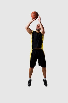 Vista frontal del jugador de baloncesto posando en el aire mientras lanza la pelota