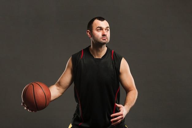 Vista frontal del jugador de baloncesto posando y jugando con pelota