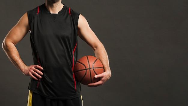 Vista frontal del jugador de baloncesto posando y sosteniendo la pelota