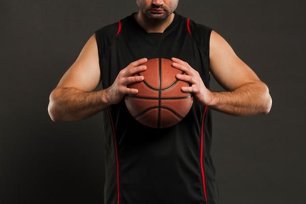 Vista frontal del jugador de baloncesto sosteniendo la pelota cerca del cofre