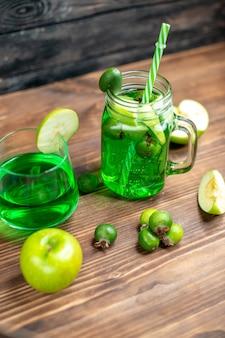 Vista frontal de jugo de feijoa verde dentro de lata con manzanas verdes en el escritorio de madera, barra, bebida de color fruta, cóctel