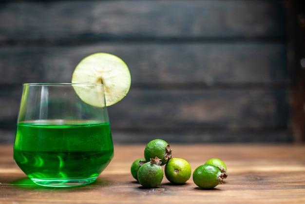 Vista frontal de jugo de feijoa verde dentro del vidrio con manzanas verdes en el escritorio de madera, barra, bebida de color fruta, cóctel