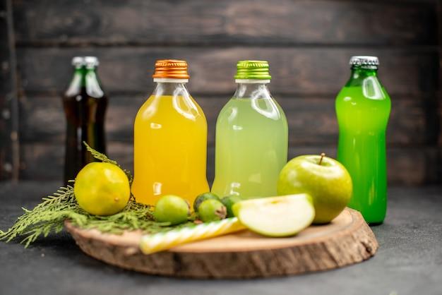 Vista frontal de jugo de fruta en botellas pipetas de feijoas de limón y manzana en limonadas de tablero de madera sobre superficie oscura