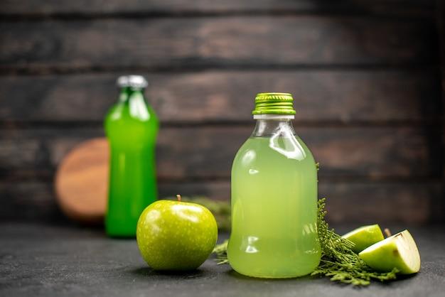 Vista frontal de jugo de manzana en botella manzana manzana cortada botella verde sobre superficie aislada de madera