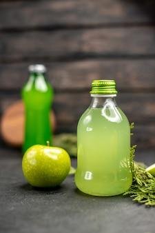 Vista frontal de jugo de manzana en botella manzana manzana cortada botella verde sobre superficie de madera