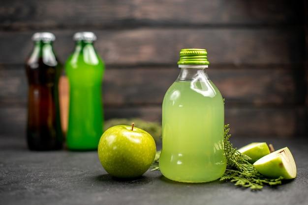 Vista frontal de jugo de manzana en botellas limonadas manzanas tablero de madera sobre superficie de madera