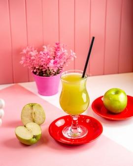 Vista frontal jugo de manzana recién exprimido con rodajas de manzana y una manzana entera