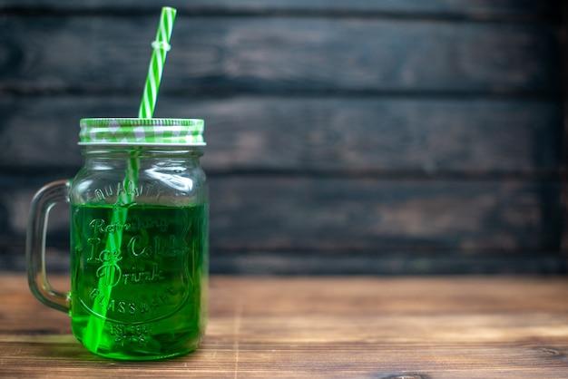 Vista frontal de jugo de manzana verde dentro de lata en el color marrón de la bebida de frutas de cóctel de fotos de madera