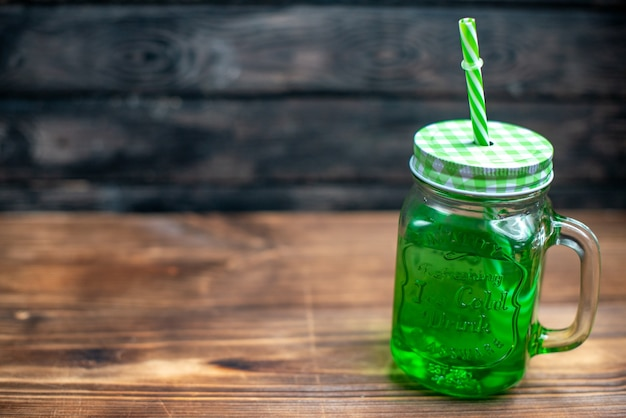 Vista frontal de jugo de manzana verde dentro de lata en el escritorio de madera bebida cóctel color fruta