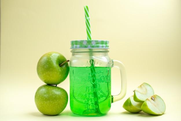 Vista frontal de jugo de manzana verde dentro de lata con manzanas frescas en un cóctel de frutas de bebida de color blanco