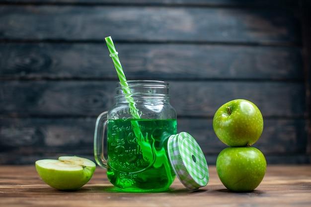 Vista frontal de jugo de manzana verde dentro de lata con manzanas frescas en color de barra de cócteles de bebida de frutas oscuras