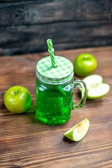 Vista frontal de jugo de manzana verde dentro de lata con manzanas frescas en el escritorio de madera, bebida de color de la foto de la fruta
