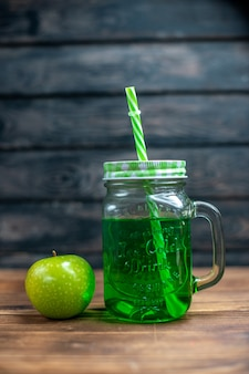 Vista frontal de jugo de manzana verde dentro de lata con manzanas verdes frescas en el escritorio de madera bebida foto barra de cócteles color de frutas