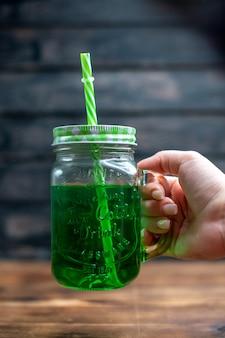 Vista frontal de jugo de manzana verde dentro de lata con pajita en el escritorio de madera bebida foto barra de cócteles color de fruta