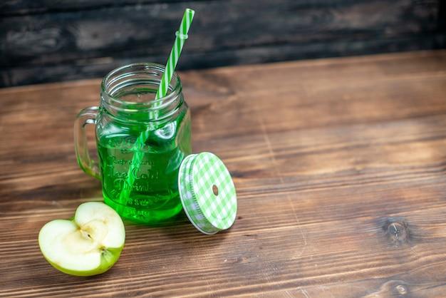 Vista frontal de jugo de manzana verde dentro de lata con una rodaja de manzana fresca en una bebida de frutas oscuras color de la barra de cócteles